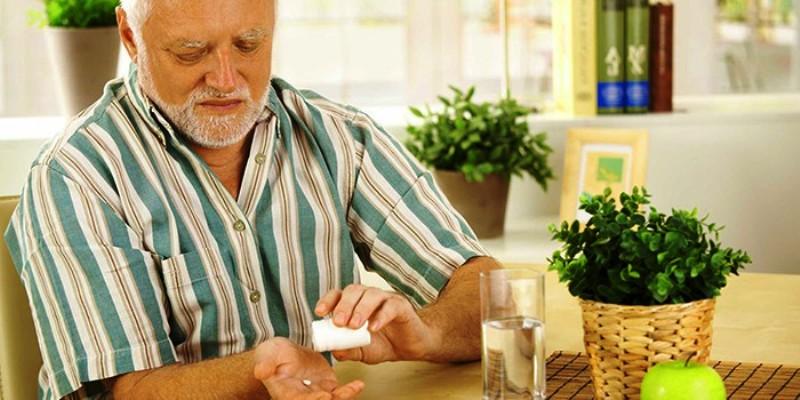 Пожилой человек принимающей таблетку